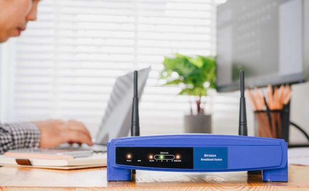 Draadloze router en man met behulp van een laptop op kantoor. router draadloos breedband thuis laptop computer telefoon wifi concept