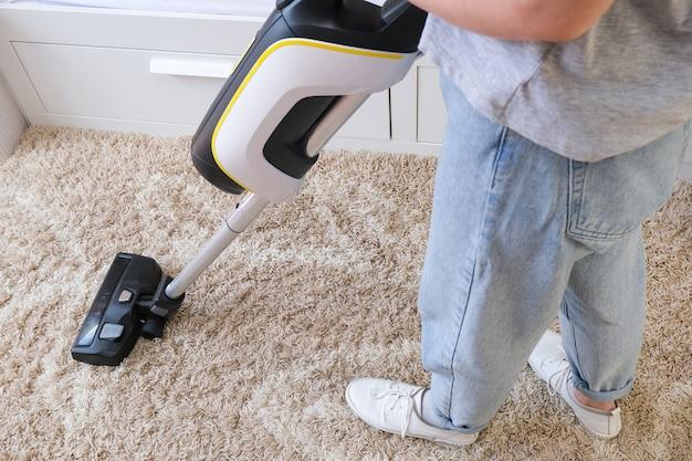 Draadloze stofzuiger wordt gebruikt om het tapijt in de kamer te reinigen. huishoudelijk werk met een nieuwe handstofzuiger. huis schoonmaken, zorg en technologie concept.