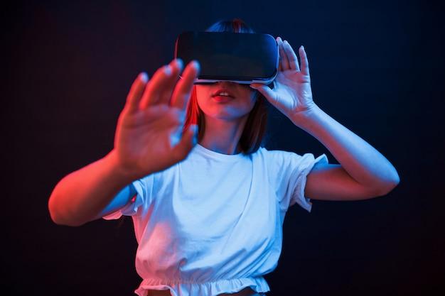 Draadloze technologieën. jonge vrouw met behulp van virtual reality-bril in de donkere kamer met neonverlichting
