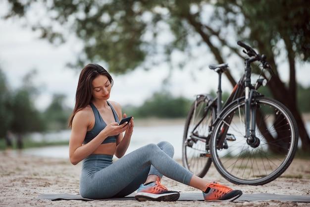 Draadloze technologieën. wielrenster met een goede lichaamsvorm zit overdag in de buurt van haar fiets op het strand