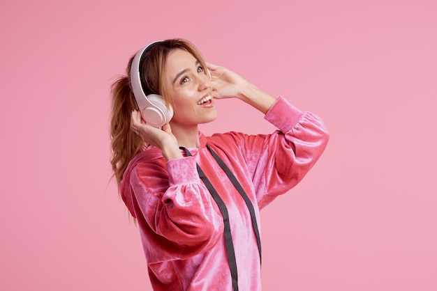 Draadloze verbinding. portret van het jonge vrouw stellen geïsoleerd over roze achtergrond het luisteren pretmuziek met hoofdtelefoons.