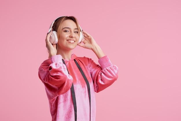 Draadloze verbinding. portret van het jonge vrouw stellen geïsoleerd over roze het luisteren pretmuziek met hoofdtelefoons.