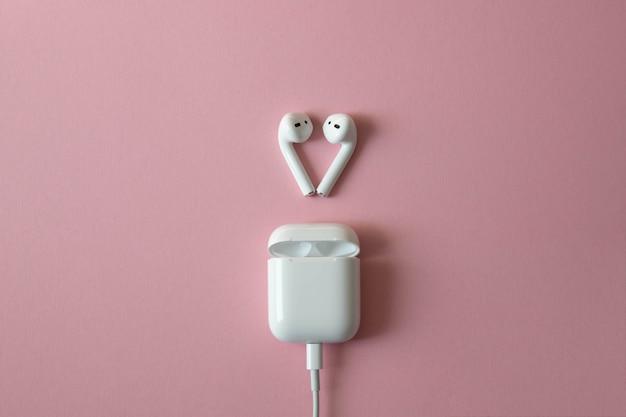 Draadloze witte hoofdtelefoon met lader aangesloten op roze achtergrond