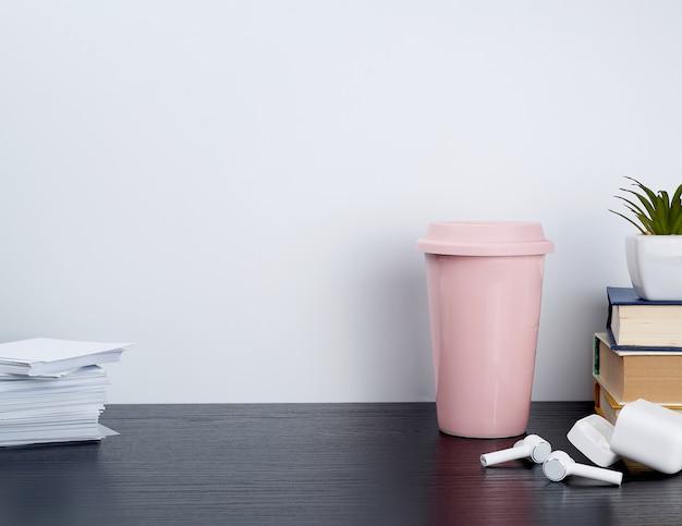 Draadloze witte koptelefoon met opladen, roze keramische kop met koffie en boeken