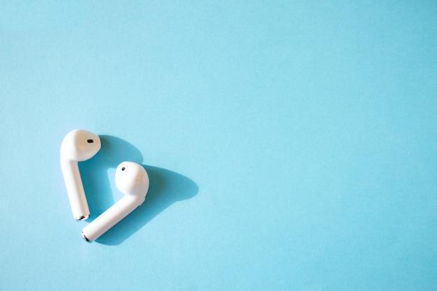 Draadloze witte koptelefoon op een blauwe muur
