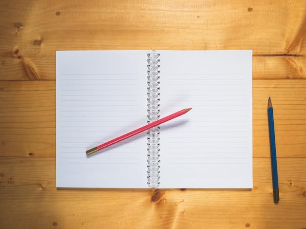 Draadnotitieboekje en potloodkleur op houten achtergrond