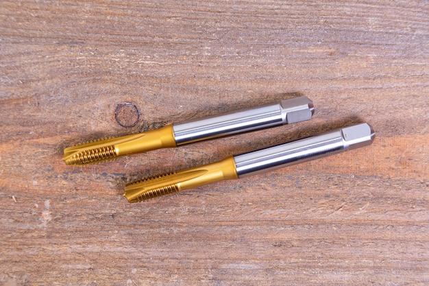 Draadsnijkranen van metaal. gereedschap voor het bewerken van metaal op een houten bord.