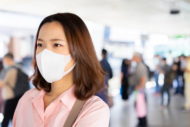 Draag een masker tijdens het wachten op het openbaar vervoer in het station om het coronavirus te beschermen