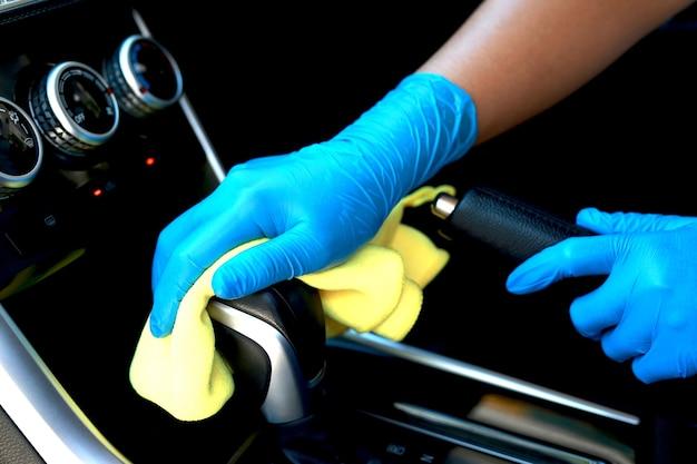 Draag handschoenen en gebruik een doek om de binnenkant van de auto schoon te maken. veeg het versnellingsgebied af