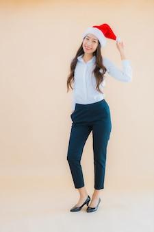 Draag kerstmishoed van de portret mooie jonge bedrijfs aziatische vrouw