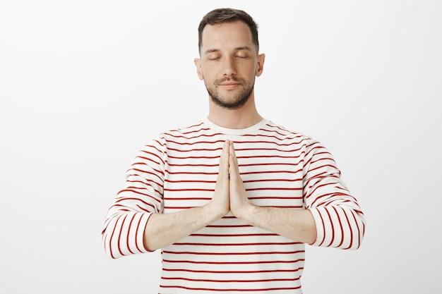 Draag slechte gedachten weg met yoga. portret van rustige ontspannen aantrekkelijke man in gestreepte pullover, hand in hand in bid en ogen sluiten