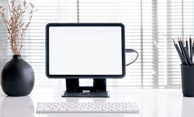 Draagbaar bureau met mock-up computerapparaten, benodigdheden en decoraties op witte tafel.