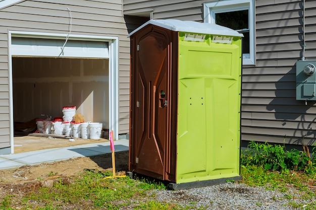 Draagbaar toilet op een nieuwe structuur dichtbij nieuw huis in aanbouw.