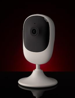 Draagbare beveiligingscamera tegen donkere ondergrond op tafel.