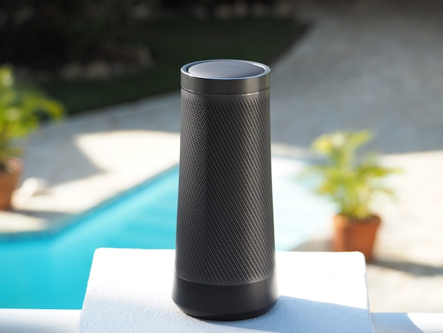 Draagbare luidspreker met stemassistent en aanraaktechnologie bij het zwembad