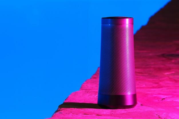 Draagbare moderne luidspreker met stemassistent 's nachts bij het zwembad