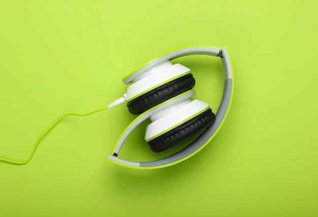 Draagbare opvouwbare stereohoofdtelefoon met smartphone op groen oppervlak