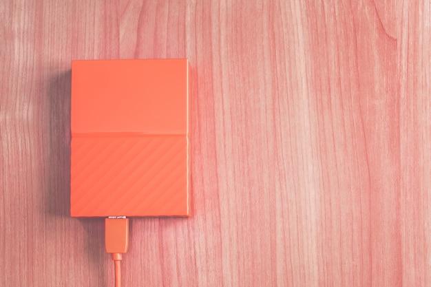 Draagbare oranje externe harde schijf op het bureau