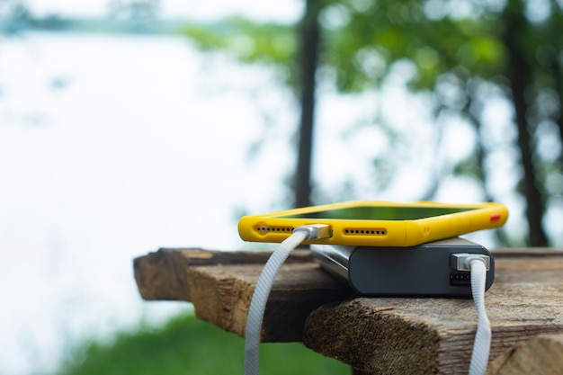 Draagbare reislader. power bank laadt een smartphone op een houten tafel, op de achtergrond van de natuur. concept op het thema van toerisme.