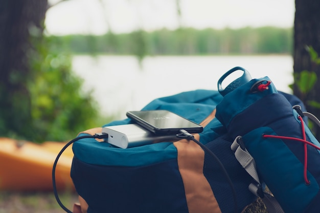 Draagbare reislader. power bank laadt smartphone op tegen een achtergrond van reistassen, een meer en bos.