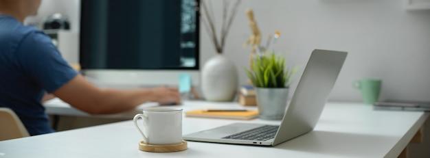 Draagbare werkruimte met laptop, beker, briefpapier en decoraties op wit bureau