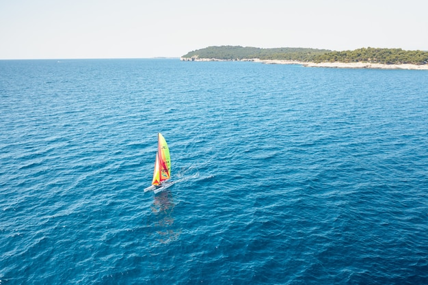 Draagbare zeilboot windsurf catamaran in het blauwe water van de adriatische zee