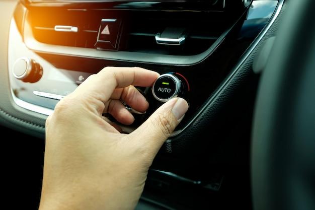 Draai de hand en pas de bedieningsknop van het airconditioningsysteem in de moderne auto aan.