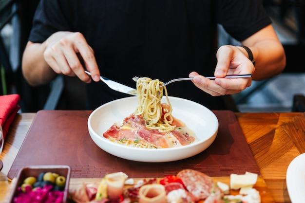 Draai met de hand de schacht van de vork en draai de strengen pasta rond de tanden voor het eten van fettuccine carbonara.