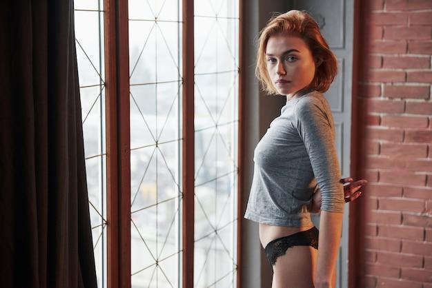Draaide haar lichaam opzij. sexy blonde meisje in ondergoed en geen beha onder het shirt poseren bij het raam in de kamer