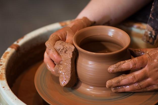 Draaiend pottenbakkerswiel en aardewerk erop bovenaanzicht een keramist maakt een pot op een pottenbakkerswiel