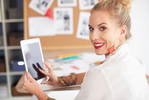 Draaiende vrouw met digitale tablet op handen