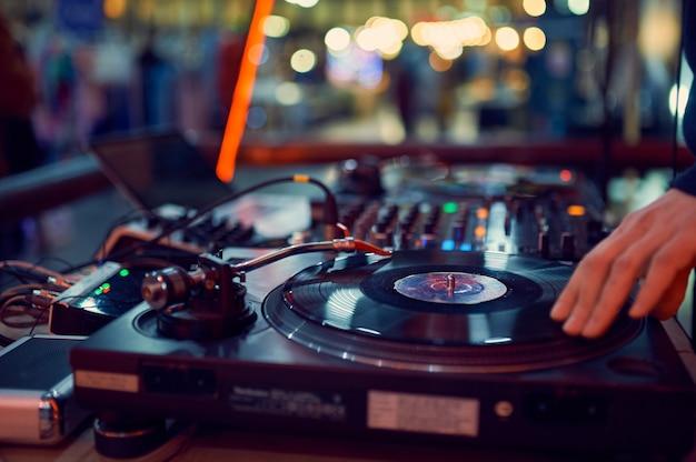 Draaitafel, hand van dj op de vinylplaat in nachtclub.