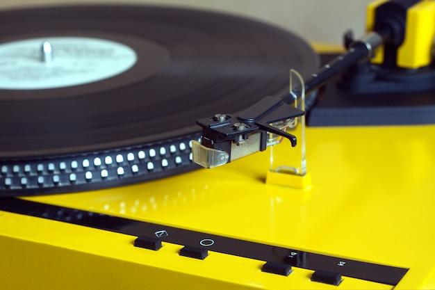Draaitafel in gele koffer waarop een vinylplaat met wit label wordt afgespeeld.