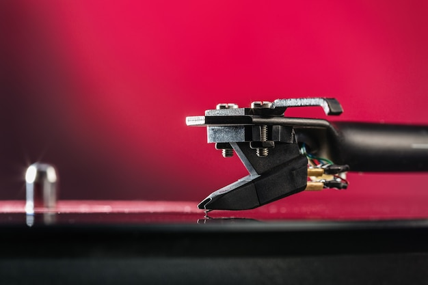 Draaitafel vinyl platenspeler. geluidstechnologie voor dj om muziek te mixen en af te spelen. vintage vinyl platenspeler op achtergrondversieringen voor feest, heldere discolichten. naald op vinylplaat