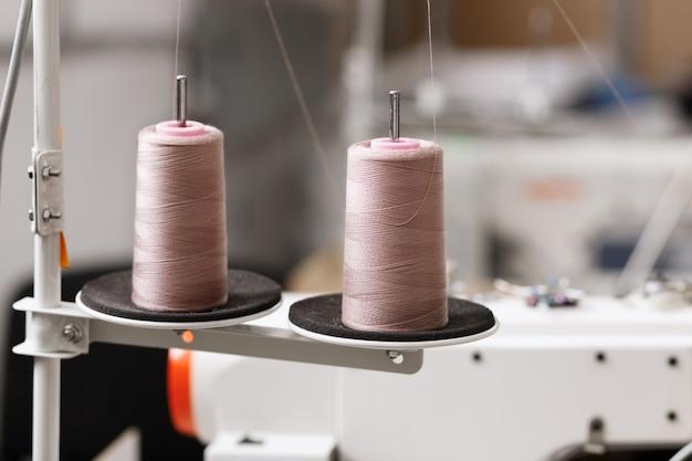 Draden in de buurt van de naaimachine in de fabriek