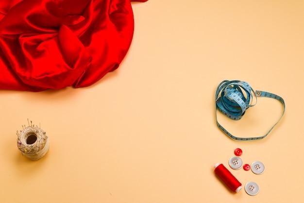 Draden, knopen, rode stof, meetlint. kopieer ruimte.