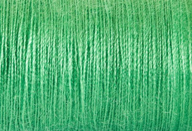 Draden naaien van groene kleur, gewikkeld in spoel, close-up macroweergave