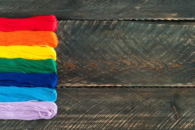 Draden voor borduurwerkzijde op de oude houten achtergrond. accessoires voor handgemaakt.