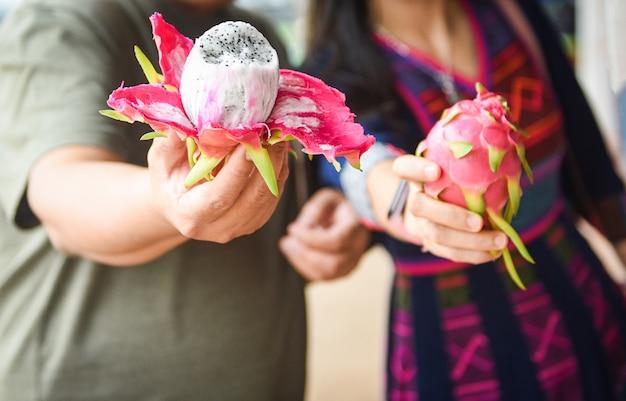 Dragon fruit in de hand man en vrouw op de fruitmarkt fresh pitaya
