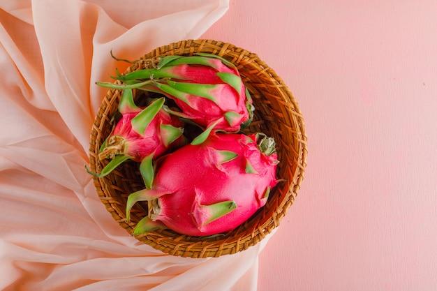 Dragon fruit in een rieten mand op roze tafel. plat lag.