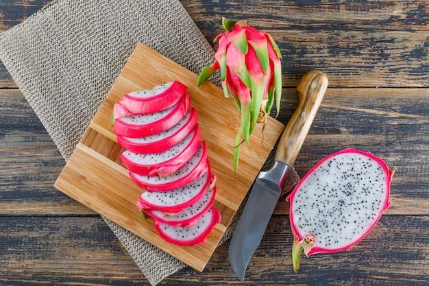 Dragon fruit met snijplank, mes plat lag op houten tafel