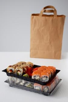 Dragon-rol en philadelphia-rol verpakt in een plastic doos voor levering in de buurt van een papieren pakket