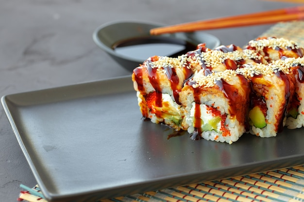 Dragon sushi roll met paling op zwarte keramische plaat close-up