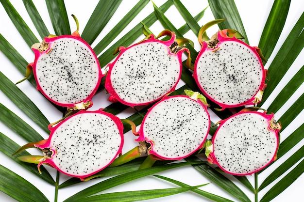Dragonfruit of pitaya op tropische palmbladeren. bovenaanzicht