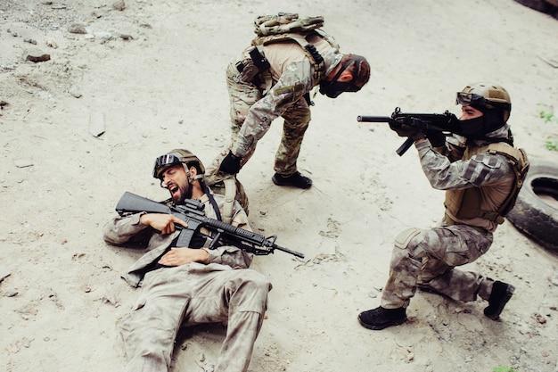 Dramatisch beeld van man raakte gewond. zijn kameraad probeert hem uit het slagveld te trekken. de derde man verdedigt ze.