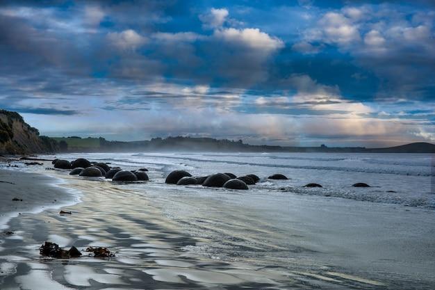 Dramatisch humeurig blauw cloudscape dat blauwe tinten weerspiegelt op het dunedin-strand en zijn iconische rotsformaties