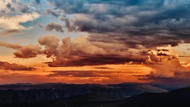 Dramatisch licht door de wolken tegen de achtergrond van een spannende, levendige stormachtige hemel bij zonsondergang, zonsopgang in de bergen.