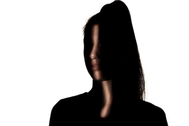 Dramatisch portret van een jong meisje in het donker dat op witte studiomuur wordt geïsoleerd