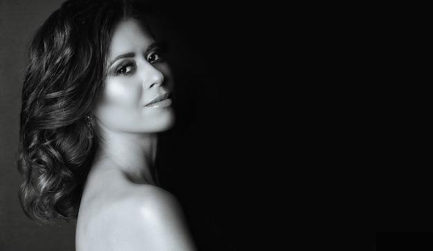 Dramatisch portret van een prachtige jonge vrouw met blote schouders poseren in de schaduw. ruimte voor tekst