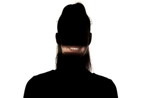 Dramatisch portret van kaukasisch jong meisje in dark dat op witte studioachtergrond wordt geïsoleerd. zonlichtlijn op het donkere gezicht. menselijke aard, verborgen dingen, psychologieconcept. kunst elegante creatieve foto.